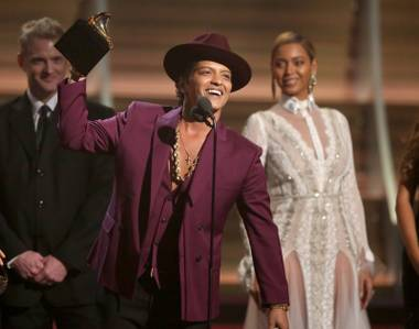 Bruno Mars accept the award for record of the year for Uptown Funk at the 58th annual Grammy Awards on Monday, Feb. 15, 2016, in Los Angeles.