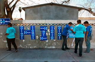 Hillary Clinton campaign volunteers work to post signs across the street from the Democratic Caucus which begins soon at Rancho High School on Saturday, February 20, 2016.
