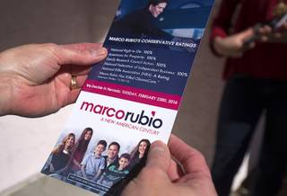A resident reads a information on Republican Presidential Candidate Sen. Marco Rubio (Fla.) as Rubio volunteers canvass a neighborhood in Summerlin Sunday, Feb. 21, 2016.