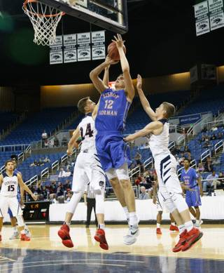 Bishop Gorman center Zach Collins (12) shoots against Coronado's Jake Desjardins (24) and Trey Hurlburt (1) during the state championship game at the Lawlor Events Center on the campus of UNR, Friday, Feb. 26, 2016.