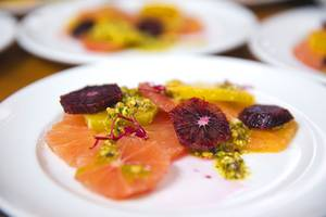 A citrus salad dish with pistachio oil is shown during a gourmet 6-course dinner at Artisanal Foods Tuesday, March 1, 2016.
