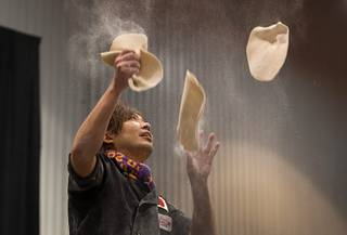 Yuya Mizuno of Japan juggles pizza dough during the World Pizza Games Freestyle Acrobatic Dough Tossing competition at the 2016 International Pizza Expo in the Las Vegas Convention Center Tuesday, March 8, 2016.