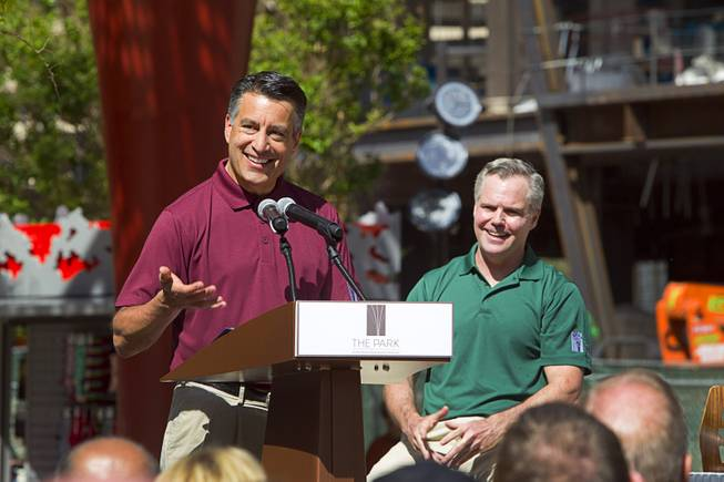 Nevada Governor Brian Sandoval, speaks during the grand opening of The Park Monday, April 4, 2016. MGM Resorts International Chairman/CEO Jim Murren listens at right. The new pocket park, lined with restaurants and seating for outdoor dining, runs from the Las Vegas Strip to the new T-Mobile Arena.