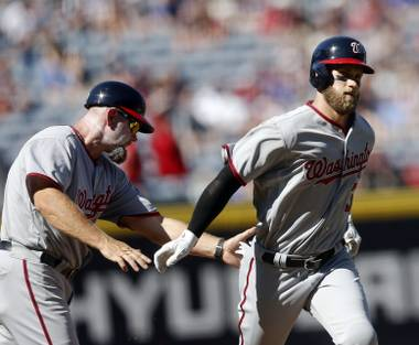 Washington Nationals' Bryce Harper, right, is greeted by third base coach Bob Henley, left, after hitting a solo-home run in the first inning of a baseball game against the Atlanta Braves, Monday, April 4, 2016, in Atlanta.