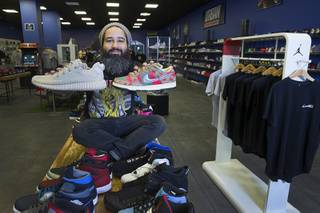 Owner Jaysse Lopez poses with some rare and pricey sneakers at Urban Necessities in the Boulevard mall Sunday, April 17, 2016. The Yeezy Oxford sneaker, left, is designed by Kanye West. At right is a rare Nike