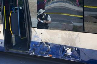 A Metro crime scene analyst ties notes at the scene of a accident between a pickup truck and a RTC bus at Sahara Avenue and McLeod Drive Sunday, April 17, 2016.