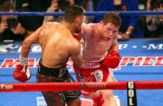 Canelo Alvarez, left, of Mexico hits Amir Khan of England with a knockout punch in the sixth round of their WBC middleweight title fight at the T-Mobile Arena Saturday, May 7, 2016.