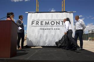 Nate Carlson (second left), vice president of development for the Wolff Company, Todd Kessler of Resort Gaming Group and Tim Wolff, executive vice president of development for the Wolff Company, unveil the name of the apartment complex during groundbreaking ceremony for Fremont9, a new apartment complex at East Fremont and Ninth streets, in downtown Las Vegas, Monday, May 16, 2016.
