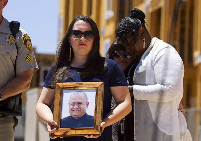 Amber Santee holds a photo of her father, Mark Santee, during a Metro Police news conference Wednesday, June 1, 2016, by an apartment complex under construction at Jerry Tarkanian Way and Hacienda Avenue. Security guard Mark Santee was shot and killed at the site in April. In the background, Metro Police's victim advocate Regina Porter, right, stands with Amber's mother, Nicole Santee.