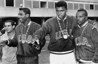 A trio of U.S. boxers wear gold medals at the Olympic village in Rome, September 6, 1960.  From the left are:  Wilbert McClure of Toledo, Ohio, light middleweight; Cassius Clay of Louisville, KY, light heavyweight; and Edward Crook of Fort Campbell, KY, middleweight.  (AP Photo)