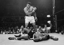 Heavyweight champion Muhammad Ali stands over fallen challenger Sonny Liston, shouting and gesturing shortly after dropping Liston with a short hard right to the jaw ...
