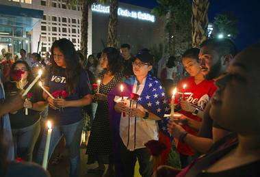 Alyssa Buhay, center, and others hold candles during a vigil and call to action at the Gay & Lesbian Community Center of Southern Nevada on Sunday, June 12, 2016, in Las Vegas. The event was a show of solidarity and support after Sunday morning's mass shooting at Pulse nightclub in Orlando, Fla., where at least 49 patrons were killed and 53 injured.