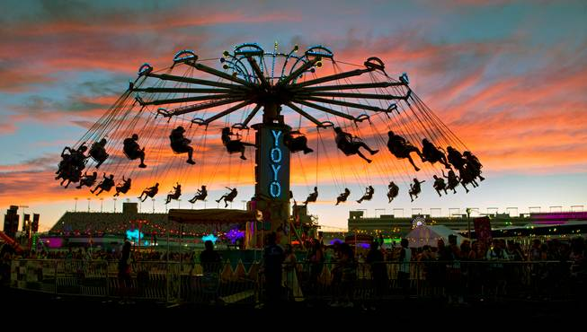 Riders on the YoYo carnival ride are silhouetted by a striking sunset during the first night of the Electric Daisy Carnival on Friday, June 17, 2016, at Las Vegas Motor Speedway.