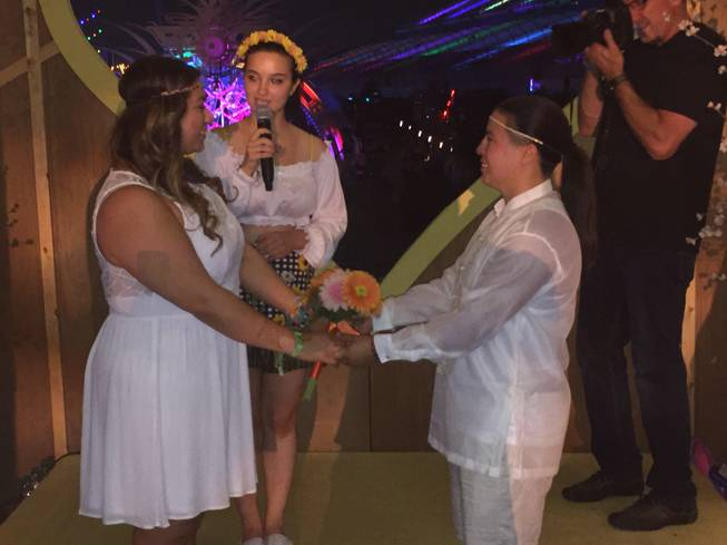 "EDC minister Jessie Tryon, 22, presides over a wedding with Maria Sisneros and Evangelina Alcantar of San Jose, Calif., at the ""Chapel of Nature"" during Night 3 of the Electric Daisy Carnival early Monday, June 20, 2016, at Las Vegas Motor Speedway."