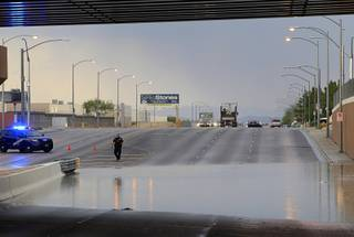 A Nevada Highway Patrol trooper stands by storm run-off at the railroad underpass on Sunset Road between Decatur Boulevard and Arville Street after a thunderstorm dropped heavy rain and hail in the area Thursday, June 30, 2016. The roadway was closed in both directions until the run-off receded.