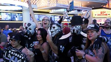 A passerby photo bombs an NFL Raiders fan photo session during a Raider Nation hosted pub crawl in Downtown Las Vegas Friday, July 22, 2016.