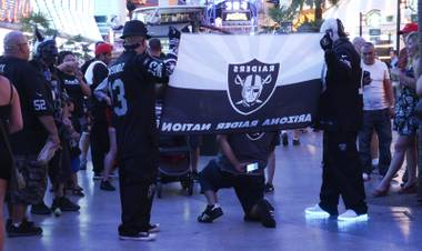 NFL Raiders fans took photos with each other during a Raider Nation hosted pub crawl in Downtown Las Vegas Friday, July 22, 2016.