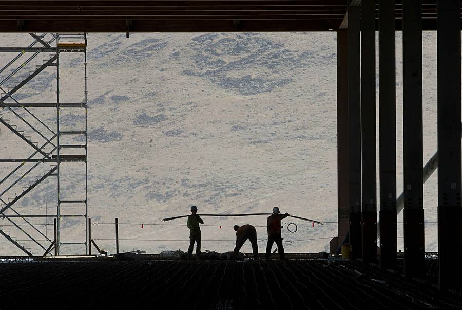 Construction workers are seen in the through uncompleted D section of new Tesla Motors Inc., Gigafactory, Tuesday, July 26, 2016, in Sparks, Nev. It's Tesla Motors biggest bet yet: a massive, $5 billion factory in the Nevada desert that could almost double the world's production of lithium-ion batteries by 2018. (AP Photo/Rich Pedroncelli)