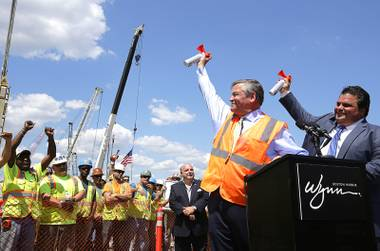 Wynn Boston Harbor President Robert DeSalvio, left, and Everett Mayor Carlo DeMaria, right, sound horns to signal an official start of construction as workers look on, left, at the site of the Wynn Boston Harbor resort casino complex, Thursday, Aug. 4, 2016, in Everett, Mass. Wynn Resorts is starting construction on its $2 billion Boston-area casino after years of legal fights.