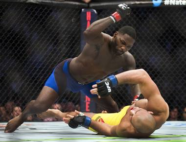 Anthony Johnson, top, landed a devastating uppercut 13 seconds into the first round to knock out Glover Teixeira in the co-main event of UFC 202 Saturday, Aug. 20, 2016, at T-Mobile Arena.