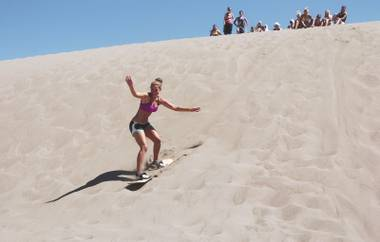 Alyssa Smith, 19, of Longmont, Colo., sandboards at Great Sand Dunes National Park and Preserve in Mosca, Colo., Saturday, Aug. 14, 2010. The Oasis shop right outside the park's main entrance rents boards for around $20 a day so you can slide down the dunes like a snowboarder, although some people choose to ride them like a sled.   (AP Photo/Thomas Peipert)