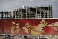 In this Friday, Aug. 26, 2016, photo, a wall with symbols of China partially blocks the view of the Resorts World property in Las Vegas. The Asian-themed casino property is projected to open in 2019.