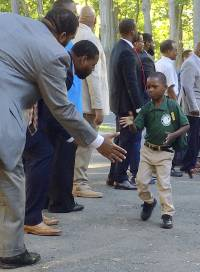 In this Tuesday, Aug. 30, 2016 photo, black professional men from the community greet students arriving for the first day of school at Martin Luther King Jr. Elementary School in Hartford, Conn. Similar welcome ceremonies have been staged for students from minority communities in cities around the country including Atlanta, Boston and Seattle.