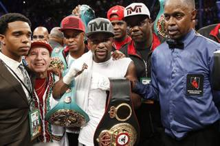Floyd Mayweather Jr., center, stands with referee Kenny Bayless, right, after defeating Andre Berto during their welterweight title boxing bout Saturday, Sept. 12, 2015, in Las Vegas.