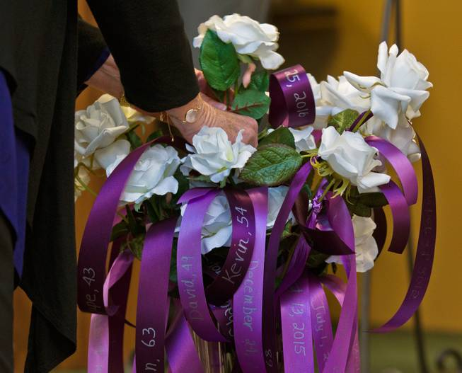 Another rose is added to a vase as victims who lost their lives due to domestic violence are remembered at a ceremony hosted by the Las Vegas Metropolitan Police Department and the Community Coalition for Victims' Rights on Thursday, Oct. 6, 2016.