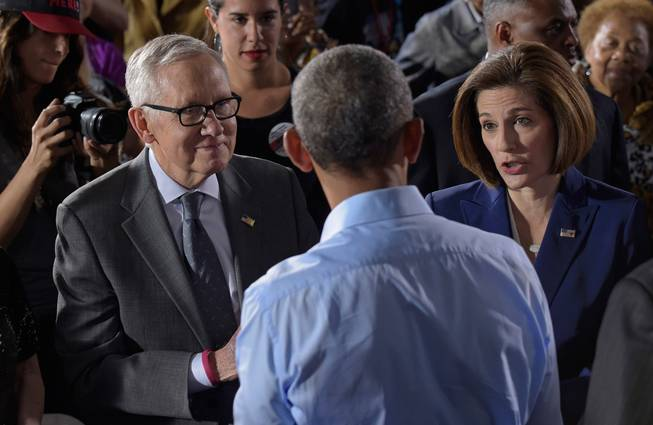 President Barack Obama, center, talks with Democratic Senate candidate Catherine Cortez Masto, right, and Senate Minority Leader Harry Reid of Nevada after speaking at Cheyenne High School in North Las Vegas on Sunday, Oct. 23, 2016, at a campaign event for Democratic presidential candidate Hillary Clinton and Cortez Masto. Obama was in Nevada to boost Clinton's presidential campaign and help Democrats in their bid to retake control of the Senate.