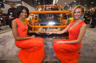 Models Tierra Benton, left, and Dani Reeves flank an light bar display at the NSV booth during the SEMA (Specialty Equipment Market Association) trade show at the Las Vegas Convention Center Thursday, Nov. 3, 2016. The light bar is a direct bolt-in for Toyota's Land Cruiser and Tundra models.