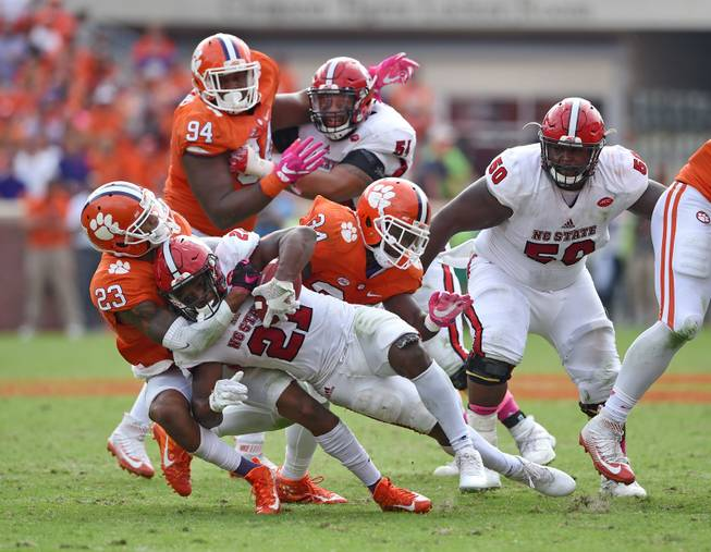 Clemson's Van Smith (21) and Kendall Joseph (34) tackle North Carolina State's Matthew Dayes during the second half of an NCAA college football game  Saturday, Oct. 15, 2016,  in Clemson,  S.C. Clemson won 24-17 in overtime.