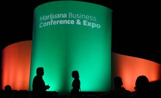 Audience members walk along the front of a stage after listening to keynote speakers during the 5th Annual Marijuana Business Conference & Expo at the Rio Hotel and Casino, Wednesday, Nov. 16, 2016.