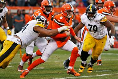 Cleveland Browns quarterback Cody Kessler, center, is tackled by Pittsburgh Steelers defensive end Stephon Tuitt, left, as he scrambles out of the pocket Sunday, Nov. 20, 2016, during the second half of an NFL game in Cleveland.