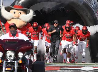UNLV Rebels head coach Tony Sanchez leads the Rebels onto the field before taking on UNR at Sam Boyd Stadium today.