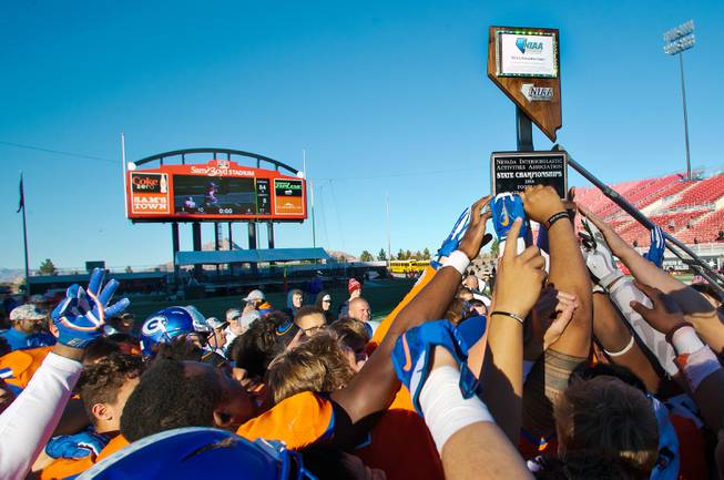 Bishop Gorman players celebrate another trophy this time over Liberty following their high school football state championship game at Sam Boyd Stadium on Saturday, Dec. 3, 2016.