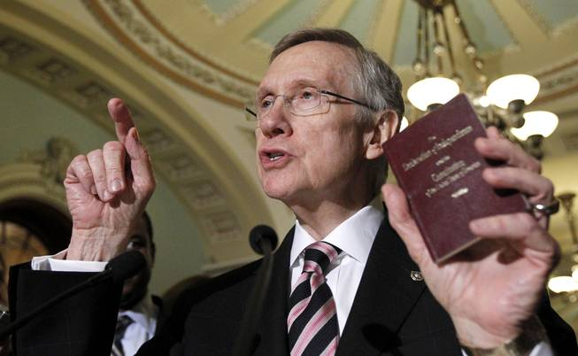Senate Majority Leader Harry Reid holds a copy of the Constitution and Declaration of Independence during a news conference on Capitol Hill in 2010.