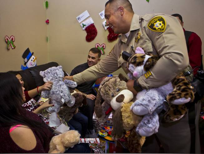 A Metro police officer  distributes stuffed animals during a Christmas party at Casa Grande Transitional Housing for children in the Las Vegas community who have parents who are incarcerated on Tuesday, Dec. 20, 2016.  It's a partnership between Hope for Prisoners and SOS Radio 90.5.
