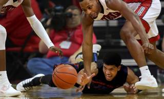 UNLV forward Cheickna Dembele (11) and Boise State guard Chandler Hutchison (15) scramble for a loose ball on the court during their game at the Thomas & Mack Center on Wednesday, Jan. 4, 2017.