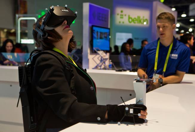 A woman spends some time enjoying an IEEE Virtual Reality device during the opening day of CES 2017 at the Las Vegas Convention Center on Thursday, Jan. 5, 2017.