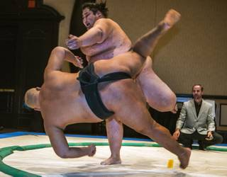 Sumo wrestler Byambajav Ulambayar is tossed from the ring by Ryuichi Yamamoto in a demonstration match during Otakon Vegas at Planet Hollywood on Saturday, Jan. 14, 2017.