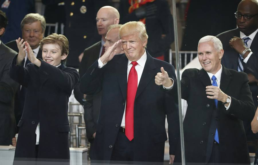 President Donald Trump, center, salute with his son Barron, left, and Vice President Mike Pence as they view the 58th Presidential Inauguration parade for President Donald Trump in Washington. Friday, Jan. 20, 2017 (AP Photo/Pablo Martinez Monsivais)