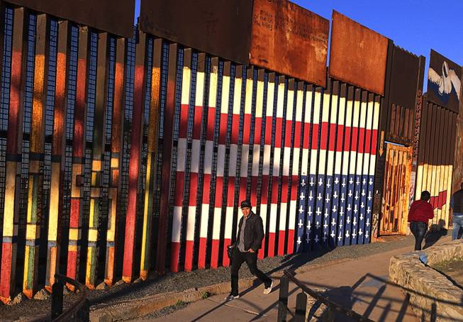 "People pass graffiti along the border structure in Tijuana, Mexico, Wednesday, Jan. 25, 2017. President Donald Trump moved aggressively to tighten the nation's immigration controls Wednesday, signing executive actions to jumpstart construction of his promised U.S.-Mexico border wall and cut federal grants for immigrant-protecting ""sanctuary cities."""