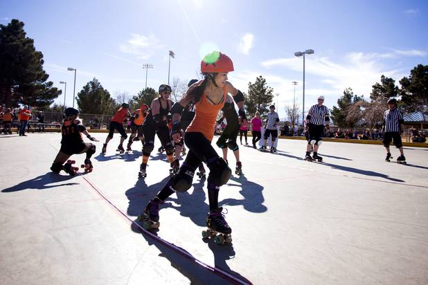Haulin, the jammer from the Orange team, skates past a block to score during the Sin City Roller Girls annual Black vs Orange season kickoff scrimmage game at West Flamingo Park, Saturday, February 4, 2017.