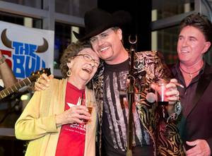 Granny Rich celebrates with her grandson John Rich during the grand opening of Redneck Riviera, a country bar in the Grand Bazaar Shops in front of Bally's, Thursday, Feb. 16, 2017. Singer T.J. Sheppard looks on at right. .