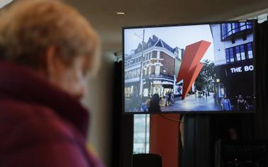 Journalists watch a TV screen that shows the virtual memorial, during a press conference to announce a permanent memorial in Brixton to the late Ziggy Stardust singer David Bowie in London, Tuesday, Feb. 21, 2017.