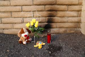 A makeshift shrine is shown against the rear wall of a northwest apartment complex Tuesday, March 14, 2017. Police are seeking the public's help after a teen's burned body was found at the complex Saturday.