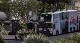 SWAT officers stage as they surround a suspect barricaded on a bus after a fatal shooting in the vehicle earlier today along the Strip outside the Cosmopolitan Hotel on Saturday, March 25, 2017.