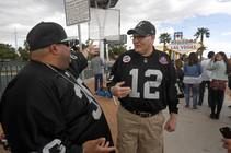Raiders fans Robert Reyes, left, of Las Vegas, and Jeff Whitaker of Ithaca, Mich. chat by the Welcome to Las Vegas sign as NFL owners ...