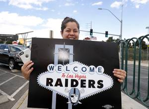 Raiders fan Brandee Chavez poses with a sign by the Welcome to Las Vegas sign after NFL owners in Phoenix voted to approve a Raiders move to Las Vegas Monday, March 27, 2017.